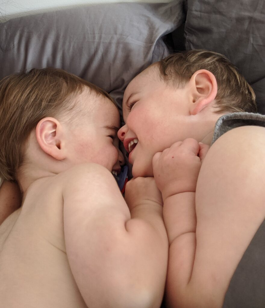 Twin brothers hugging while smiling.