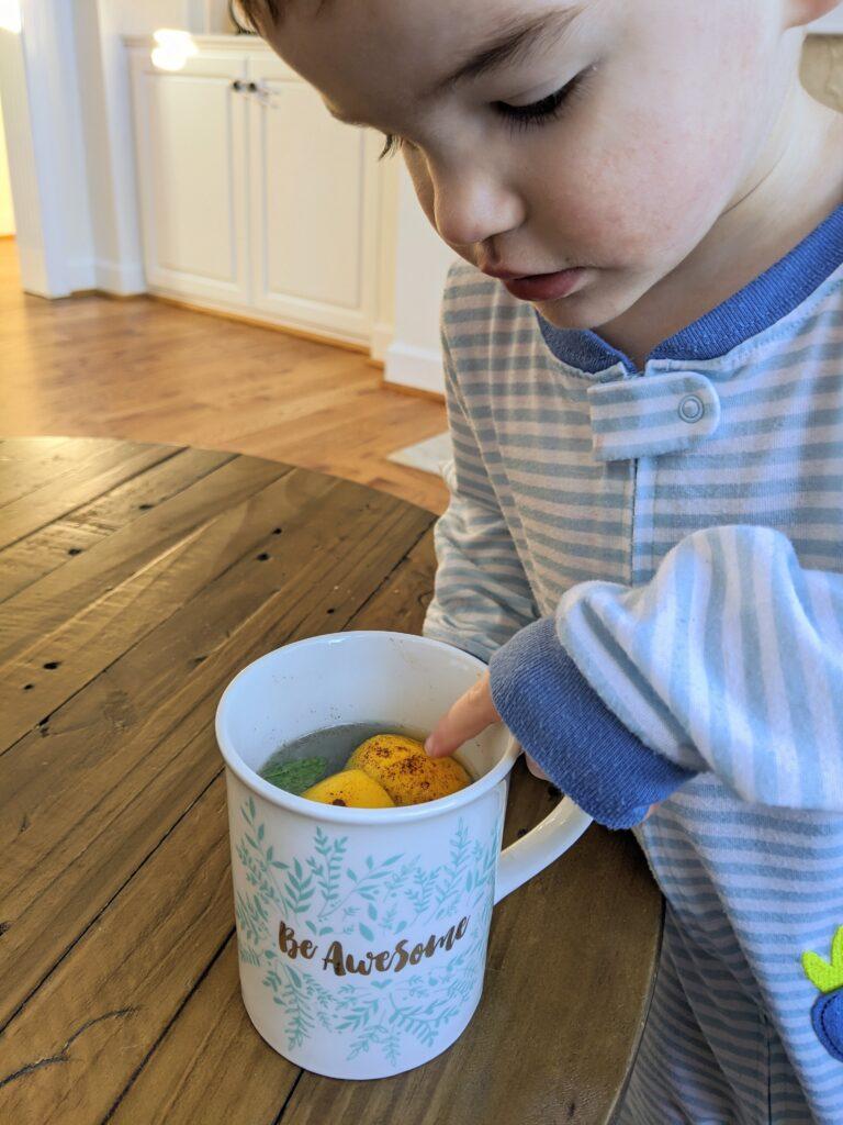 Toddler pointing at lemon water
