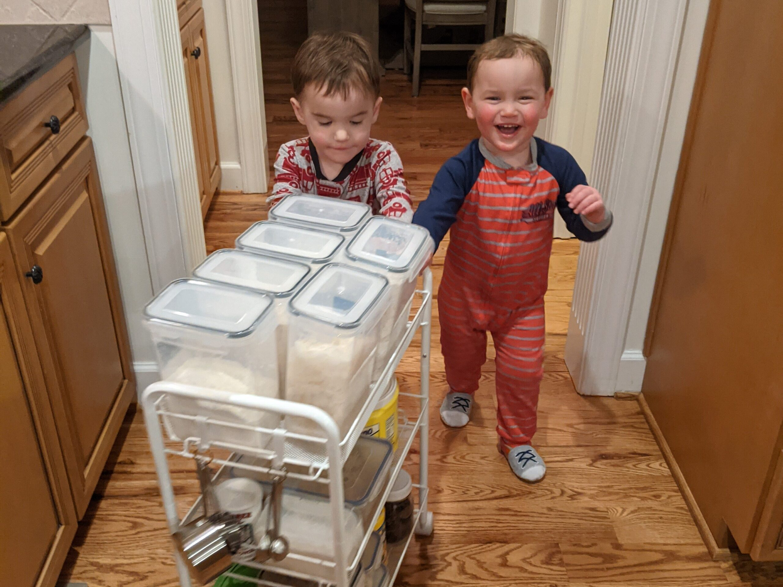 Twin toddlers pushing an organized cart of baking supplies